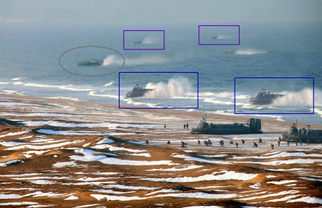 2 The hovercraft depicted inside the boxes in this image released by KCNA appear to be digital clones of each other, most evident in the blue boxes, where the leftmost hovercraft has apparently been copied, pasted and touched up to become a separate hovercraft at right. The leftmost vehicle, circled, does not appear to be a clone of any other craft in this photo, but its soft edges, lack of a visible wake, and color oddities make the image suspect. (Click here to view image at original size, 2600x1726) (KCNA Via KNS/AFP/Getty Images) #
